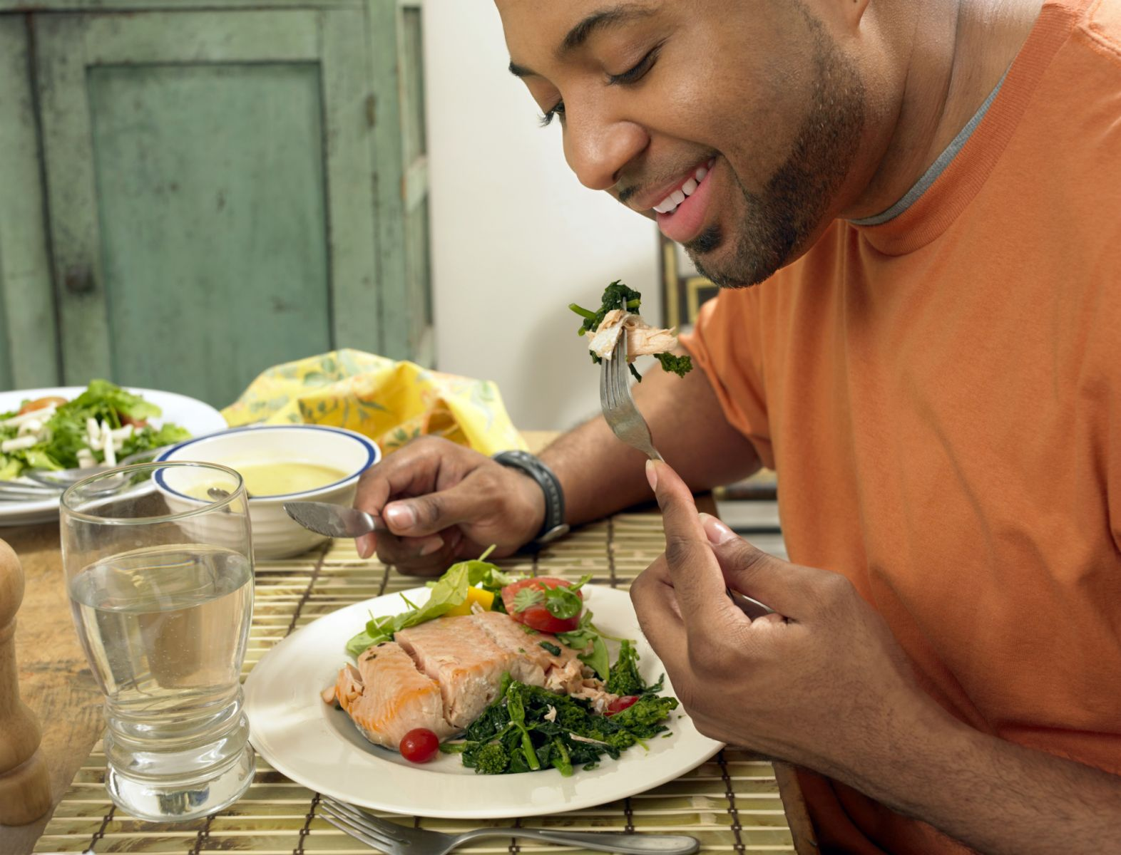 Man eating salmon , a good source of heart-protecting omega-3 fatty acides