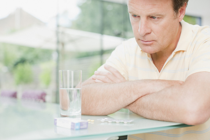 man-with-water-and-box-of-pills