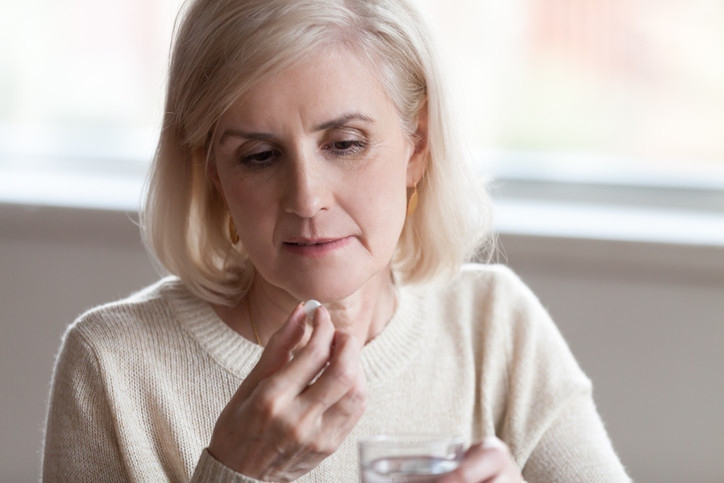 older-woman-holding-pill-and-glass-of-water
