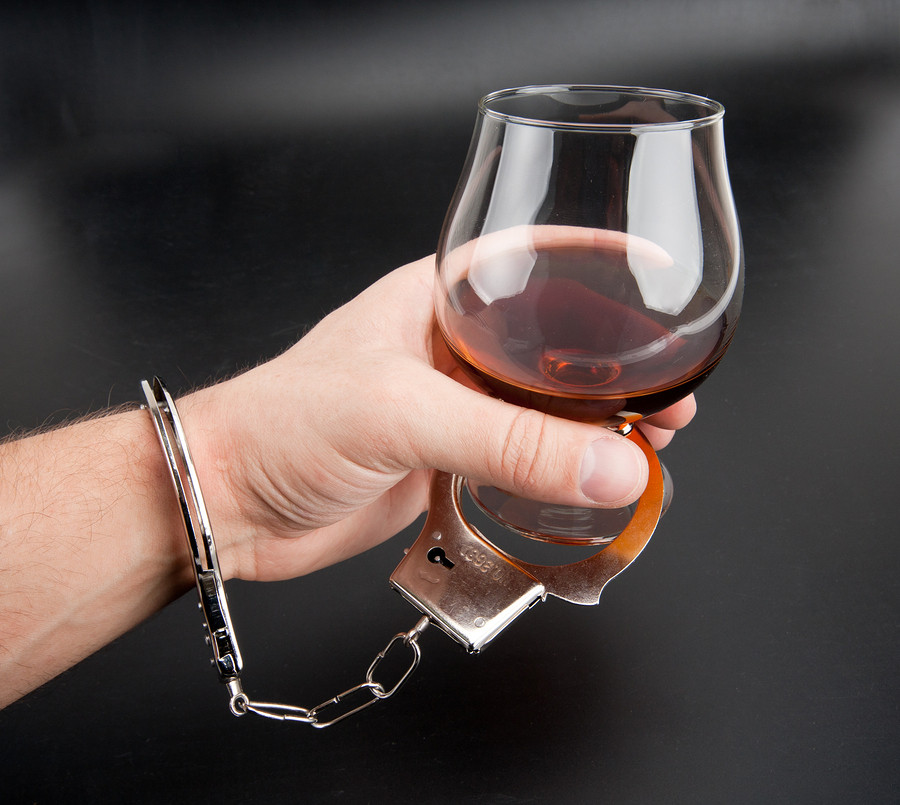 bigstock-A-Hand-Locked-To-Glass-Of-Alco-13387529
