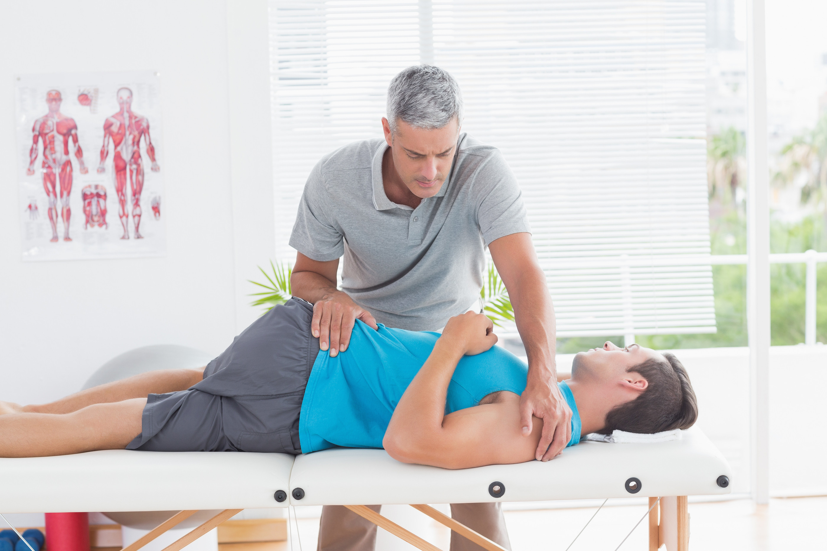 bigstock-physical-therapist-stretching-lower-back-man-85571219
