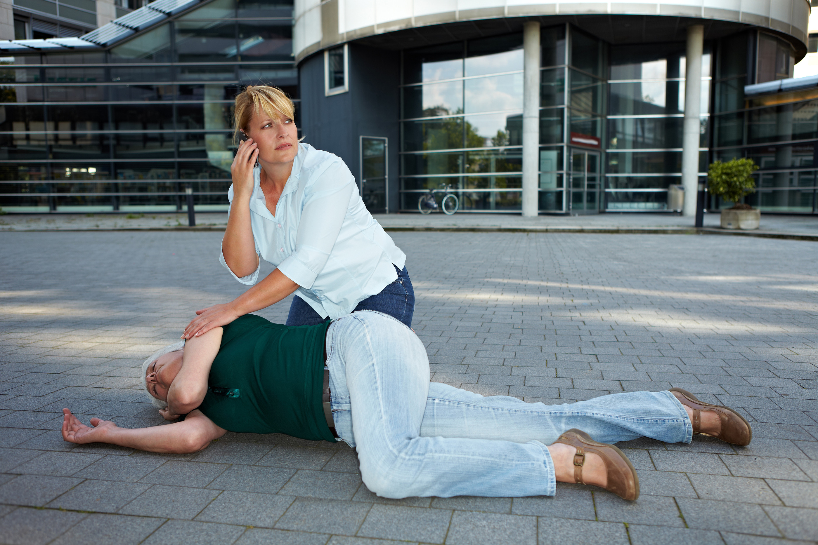 fainting-Passerby-Making-Emergency-Call-23636249