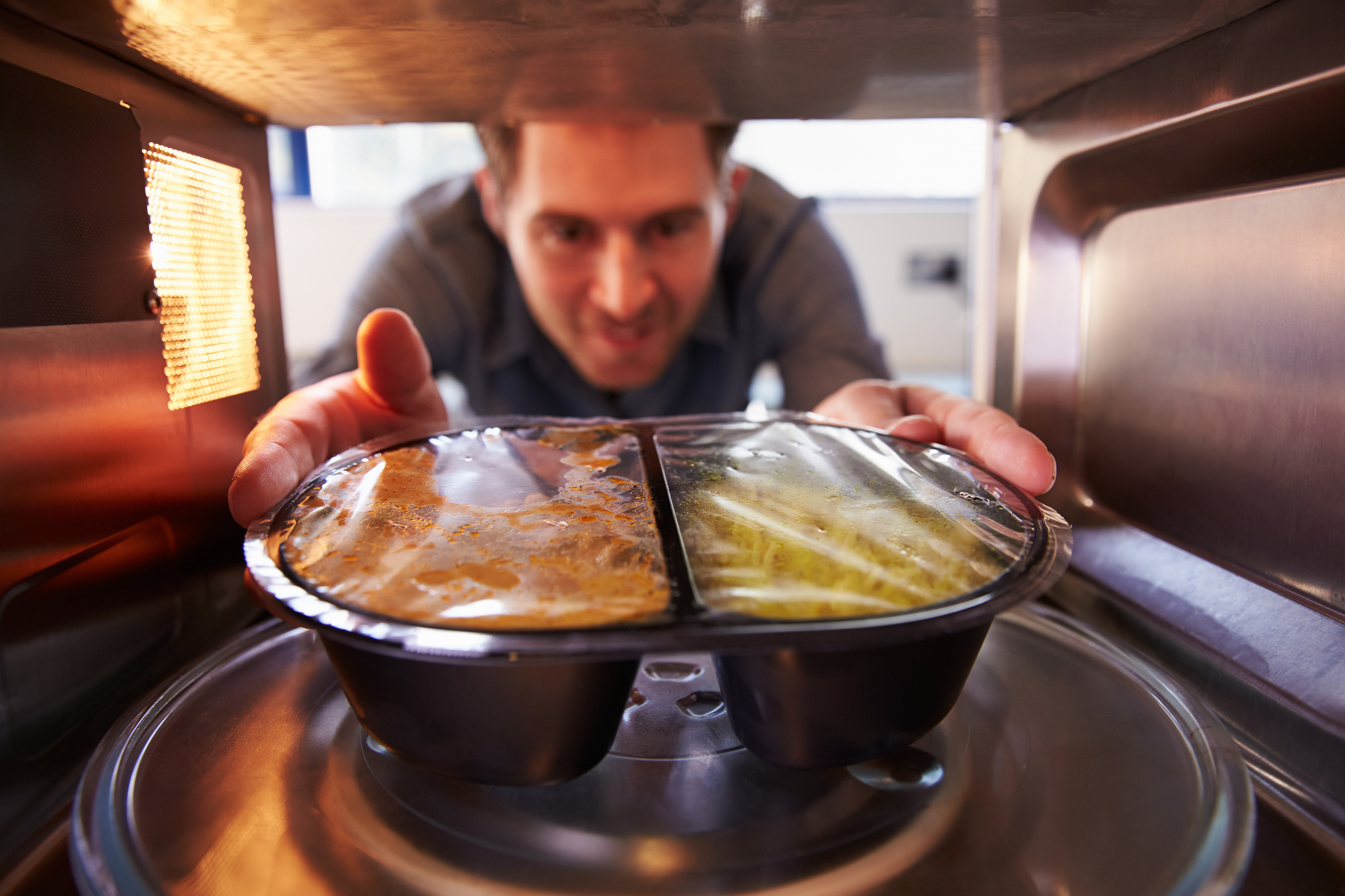 bigstock-Man-microwave-Dinner-Into-Mic-77372021