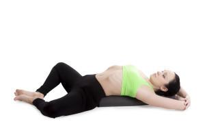 Sporty girl on white background resting in Reclining Bound Angle yoga Pose, Supta Baddha Konasana, restorative, relaxing asana, using bolster