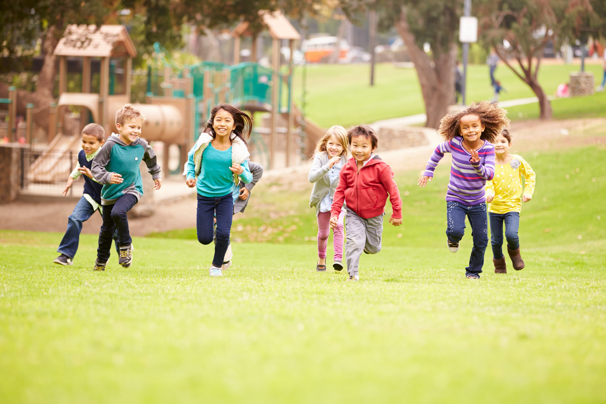 children running in a field with a playground behind them