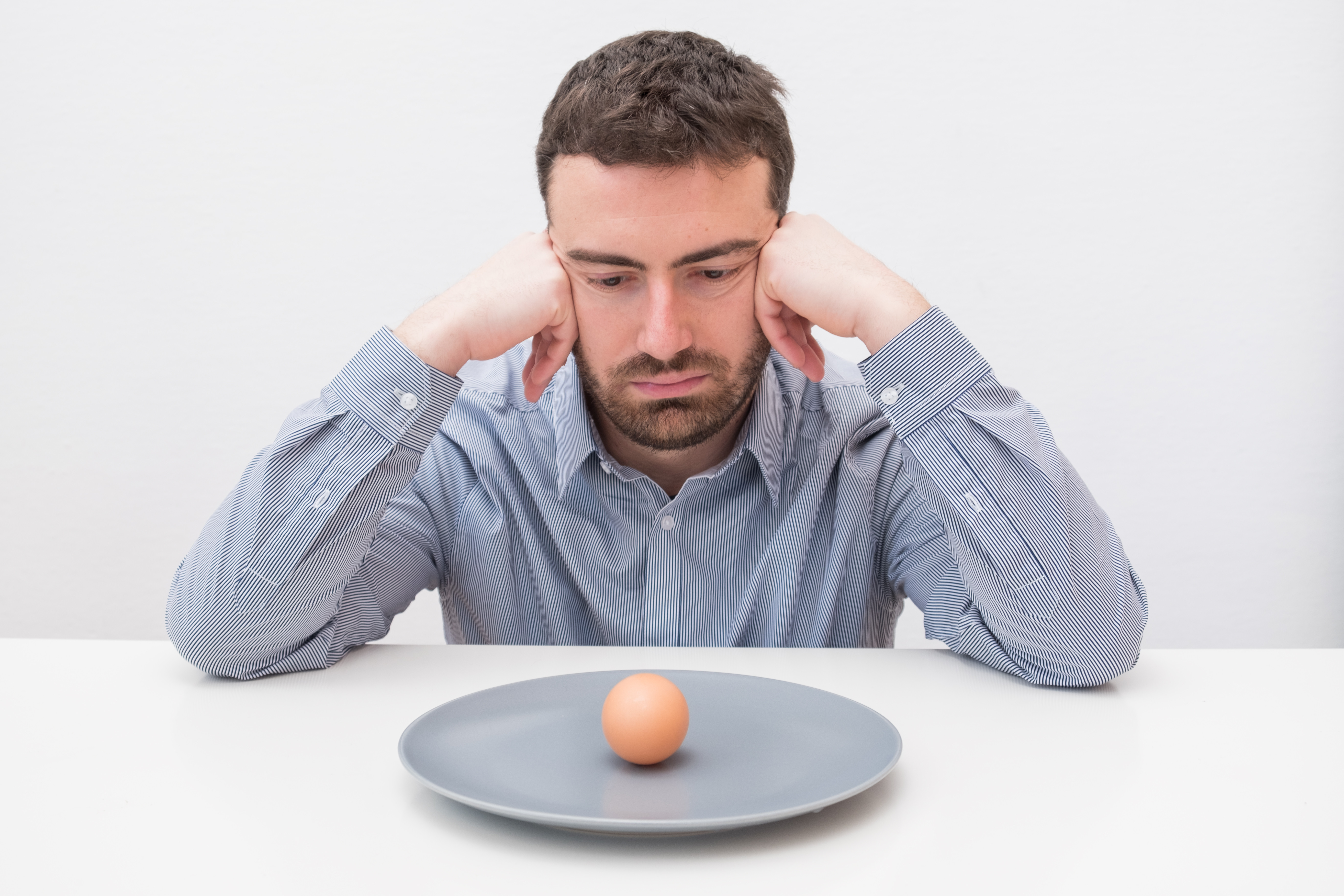 man-looking-at-egg-on-plate