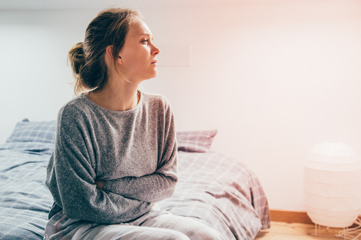 young-woman-on-bed-looks-tired-and-unwell